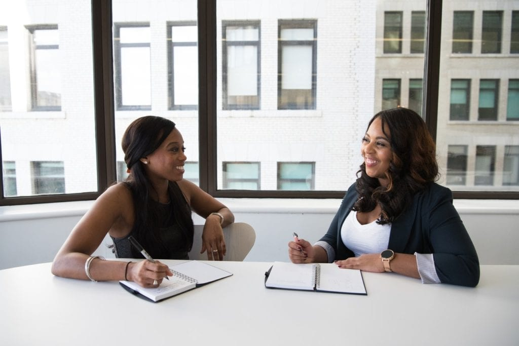 two business women sitting in front of a large glass window discussing bringing on a dedicated CPA to handle their business finances.