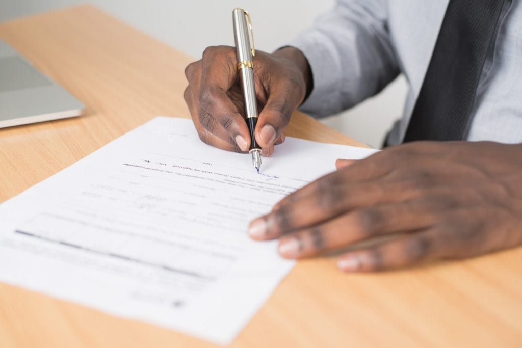 man signing document on desk, finalizing estate paperwork for their loved one who has passed