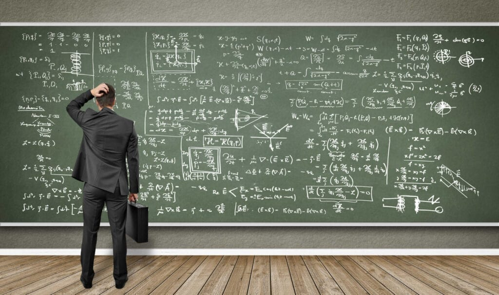 man standing in front of a blackboard scratching his head